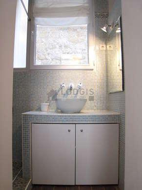 Belle salle de bain claire avec fenêtres et du dallage au sol
