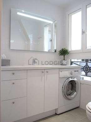 Agréable salle de bain claire avec fenêtres double vitrage et du carrelage au sol
