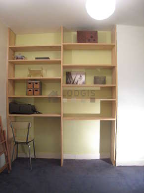 Office with a carpeting floor furnished with shelves