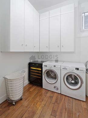 Très belle buanderie avec du parquet au sol et équipée de lave linge, sèche linge