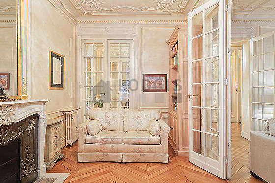 Très beau bureau avec du parquet au sol, équipé de canapé, bibliothèque, etagère