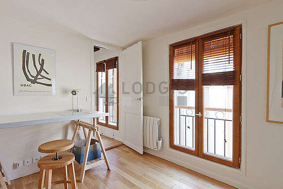 Beautiful office with wooden floor furnished with desk, cupboard