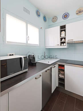 Kitchen equipped with washing machine, refrigerator, cookware