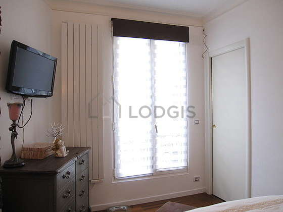 Bright bedroom equipped with tv, 1 chair(s), stool
