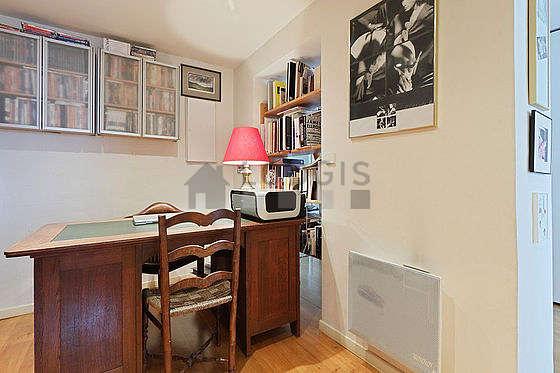 Beau bureau de 10m² avec du parquet au sol, équipé de bureau, bibliothèque, etagère
