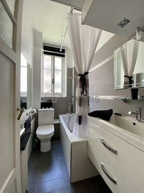 Agréable salle de bain claire avec fenêtres et du linoleum au sol
