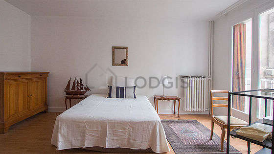 Bright bedroom equipped with tv, 1 armchair(s), bedside table