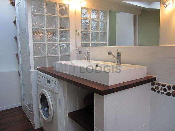 Agréable salle de bain claire avec fenêtres et du parquet au sol