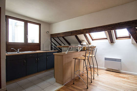 Beautiful kitchenopens on the living room with tile floor