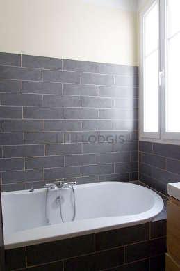 Salle de bain équipée de lave linge, baignoire, sèche cheveux