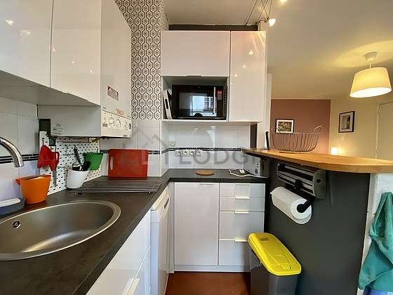 Kitchen equipped with hob, refrigerator, crockery