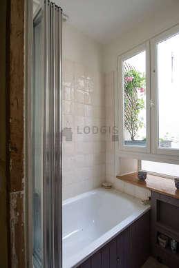 Salle de bain claire avec fenêtres et des tomettes au sol