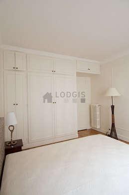 Chambre lumineuse équipée de placard, table de chevet