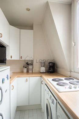 Kitchen equipped with washing machine, refrigerator, stool