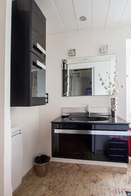 Agréable salle de bain claire avec fenêtres et du granit au sol