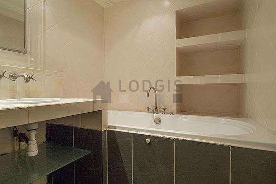 Salle de bain équipée de baignoire, douche séparée, radiateur sèche-serviettes