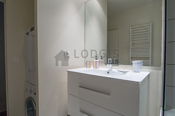 Bathroom equipped with washing machine, dryer, shower in bath tub
