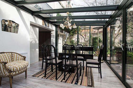 Agréable véranda de 18m² avec du parquet au sol et une vue sur jardin