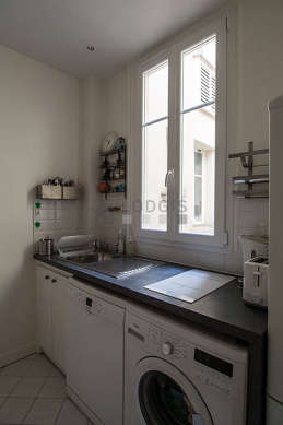 Kitchen equipped with washing machine, refrigerator, cookware, stool