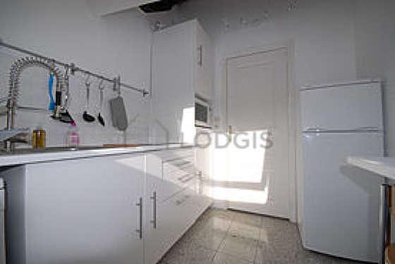 Cuisine équipée de lave linge, réfrigerateur, tabouret