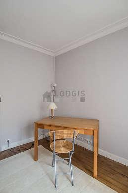 Beau bureau avec du parquet au sol, équipé de 1 fauteuil(s)
