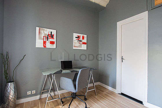 Beautiful office with wooden floor furnished with 1 armchair(s)