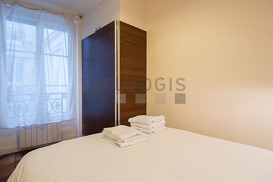 Bright bedroom equipped with wardrobe, bedside table