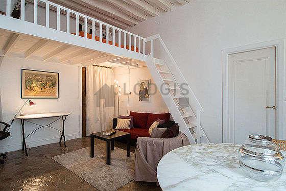 Grand salon de 23m² avec des tomettes au sol