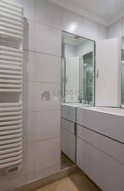 Bathroom equipped with washing machine, separate shower, towel drying radiator