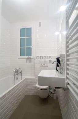 Agréable salle de bain avec fenêtres double vitrage et du béton au sol