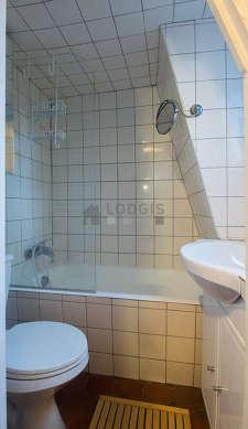 Salle de bain claire avec fenêtres double vitrage et des tomettes au sol