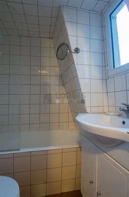 Salle de bain équipée de baignoire, radiateur sèche-serviettes