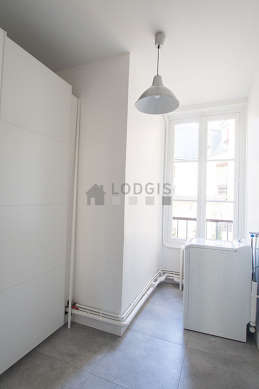 Beautiful laundry room with tile floor and equipped with washing machine