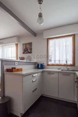Kitchen equipped with dishwasher, hob, refrigerator, extractor hood