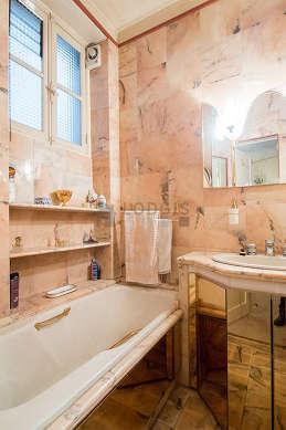 Belle salle de bain claire avec fenêtres et du marbre au sol