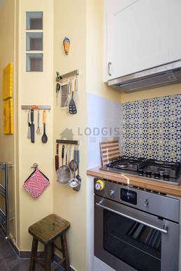 Cuisine équipée de plaques de cuisson, hotte, vaisselle