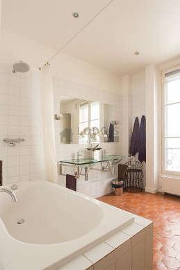 Belle salle de bain claire avec des tomettes au sol