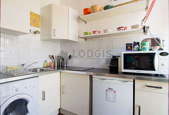 Kitchen equipped with washing machine, extractor hood