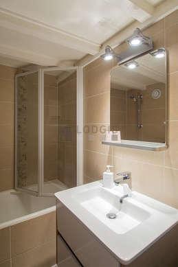 Salle de bain équipée de baignoire, sèche cheveux