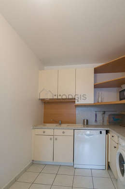 Kitchen equipped with washing machine, refrigerator, hood