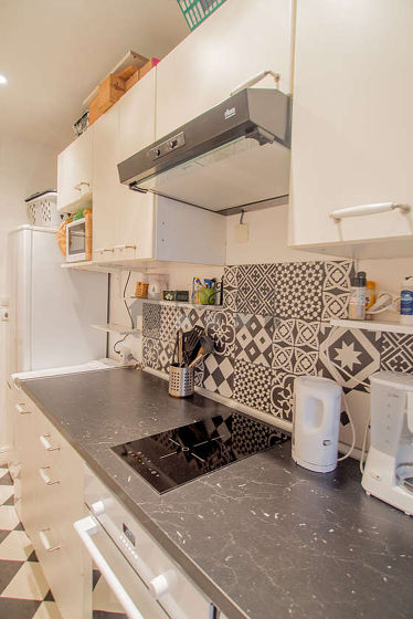 Kitchen equipped with washing machine, extractor hood, crockery, stool