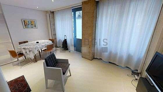 Grand salon de 30m² avec du béton au sol