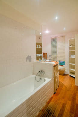 Agréable salle de bain claire avec fenêtres double vitrage et du parquet au sol