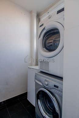 Très belle buanderie avec du carrelage au sol et équipée de lave linge, sèche linge, congélateur