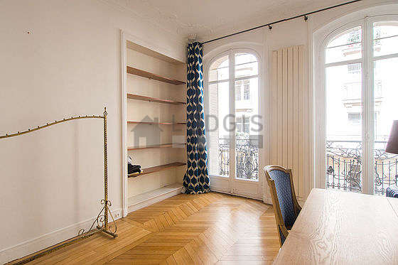 Very beautiful office with wooden floor furnished with desk, shelves