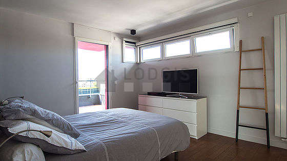Very bright bedroom equipped with tv, bedside table