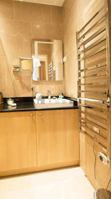 Salle de bain équipée de douche séparée, radiateur sèche-serviettes