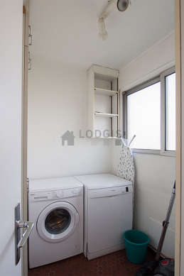 Laundry room with floor tiles floor and equipped with washing machine, dryer