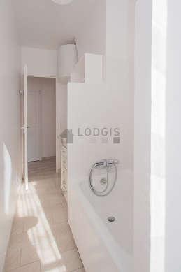 Salle de bain très claire avec fenêtres et du carrelage au sol