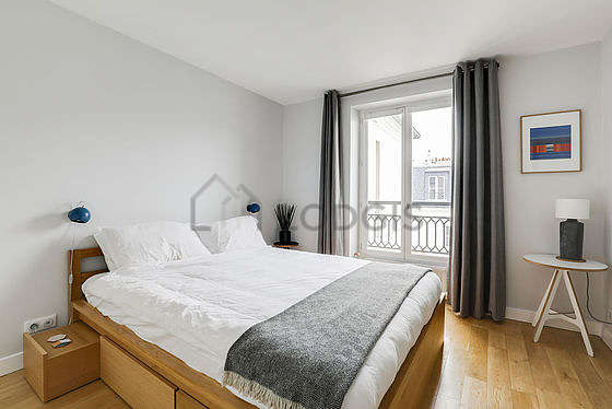 Very bright bedroom equipped with fan, bedside table